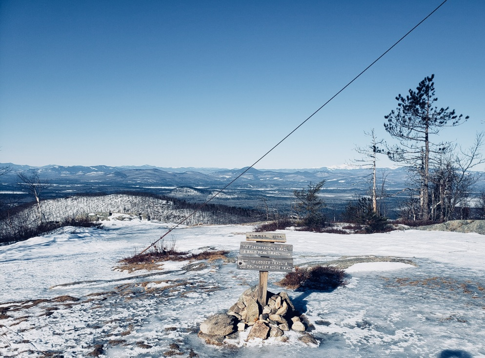 Pleasant Mountain summit in winter, with observation tower guideline and Mount Washington in background
